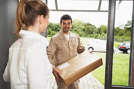 Delivery Person Giving Package to Woman Stock Photo - Rights-Managed, Code: 700-01716481
