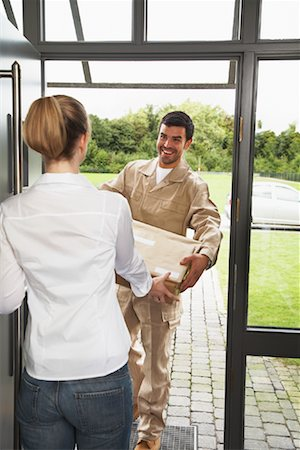 Delivery Person Giving Package to Woman Stock Photo - Rights-Managed, Code: 700-01716482