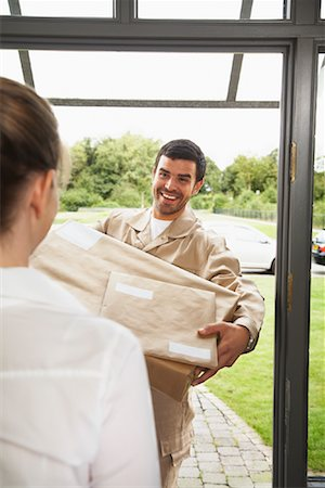 Delivery Person Giving Package to Woman Stock Photo - Rights-Managed, Code: 700-01716483