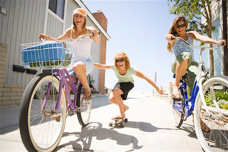 southern california - Women Riding Bicycles, Pulling Woman on Skateboard, Newport Beach, Orange County, California, USA Stock Photo - Rights-Managed, Code: 700-01837371