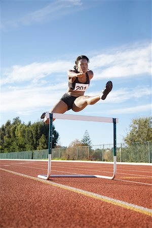 Woman Jumping over Track Hurdle Stock Photo - Rights-Managed, Code: 700-01880224