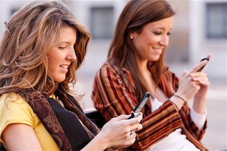 Women with Cellular Phones on Bench, Zaragoza, Spain Stock Photo - Rights-Managed, Code: 700-02063694