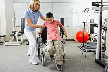 Physiotherapist Helping Boy out of Wheelchair Stock Photo - Rights-Managed, Code: 700-02071749