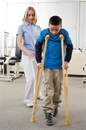 rehabilitation - Female Physiotherapist Helping Boy on Crutches Stock Photo - Rights-Managed, Code: 700-02071741