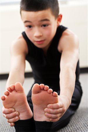 Boy Sitting on Floor Stretching Stock Photo - Rights-Managed, Code: 700-02071757