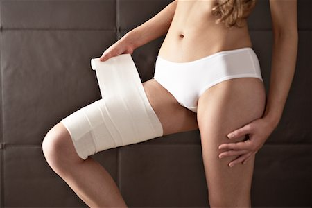 Woman Wrapping Bandage Around Thigh Stock Photo - Rights-Managed, Code: 700-02245029