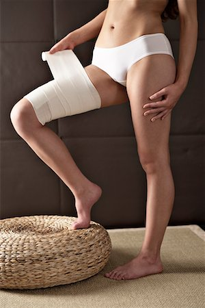 Woman Wrapping Bandage Around Thigh Stock Photo - Rights-Managed, Code: 700-02245030