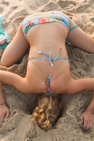 Teenaged Girl Sticking Head Into Hole in the Sand Stock Photo - Rights-Managed, Code: 700-02263993