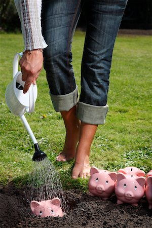Woman Watering Piggy Banks Stock Photo - Rights-Managed, Code: 700-02289303