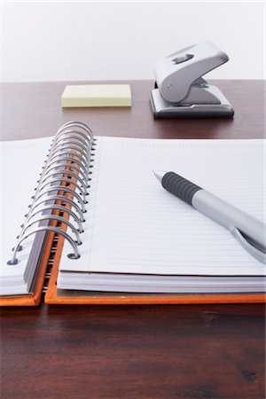 school desk - Pen and Day Planner, Hole Puncher and Sticky Notes in the Background Stock Photo - Rights-Managed, Code: 700-02371523