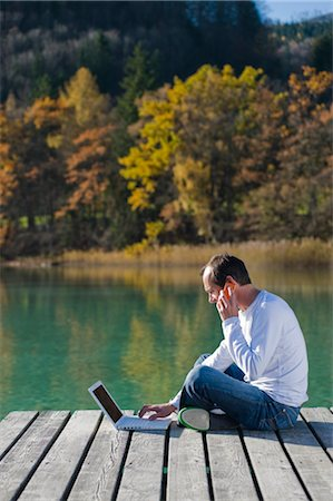 Man Sitting on Dock, Talking on Cell Phone and Using Laptop, Fuschlsee, Fuschl am See, Salzburger Land, Austria Stock Photo - Rights-Managed, Code: 700-02428742