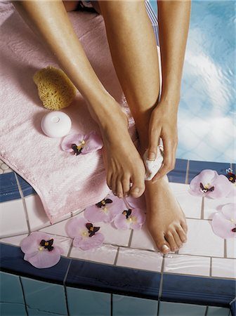 Woman Scrubbing Feet by Pool Stock Photo - Rights-Managed, Code: 700-02461225