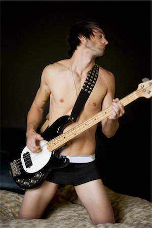Man Playing Bass Guitar on Bed Stock Photo - Rights-Managed, Code: 700-02594139