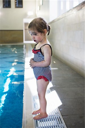 Nervous Little Girl Standing on Edge of Swimming Pool Stock Photo - Rights-Managed, Code: 700-02633620