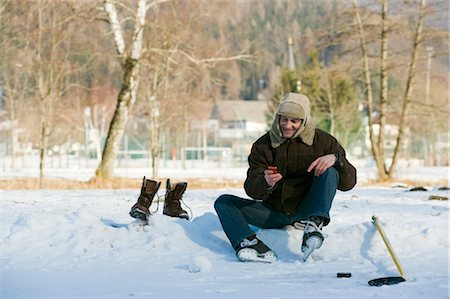 Man Sitting by Ice Rink Looking at Cell Phone, Fuschl am See, Salzburg, Austria Stock Photo - Rights-Managed, Code: 700-02670590