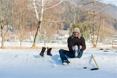 Man Tying Skate Laces by Ice Rink, Fuschl am See, Austria Stock Photo - Rights-Managed, Code: 700-02670591