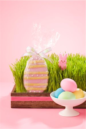 Egg Shaped Easter Cookie in Grass Filled Tray with Marshmallow Bunny and Dish of Dyed Eggs Stock Photo - Rights-Managed, Code: 700-02694064