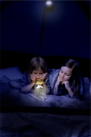 Girls in Tent at Night Looking at Jar of Fireflies Stock Photo - Rights-Managed, Code: 700-02698406