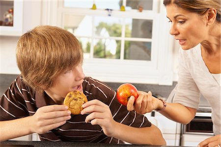 Mother Trying to Get Son to Eat an Apple Instead of a Cookie Stock Photo - Rights-Managed, Code: 700-02738797