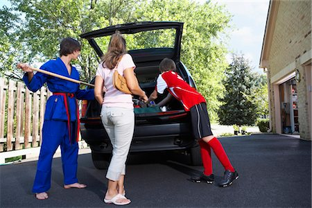 Boys in Karate and Soccer Uniforms Helping Mom Pack the Car Stock Photo - Rights-Managed, Code: 700-02738850