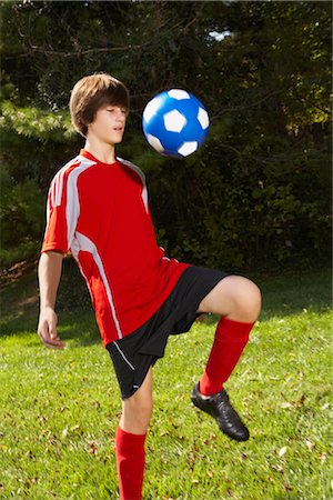 Teenage Boy Bouncing Soccer Ball on Knee Stock Photo - Rights-Managed, Code: 700-02757194