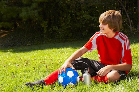 Teenage Boy in Soccer Uniform Sitting on Grass with Soccer Ball Stock Photo - Rights-Managed, Code: 700-02757196