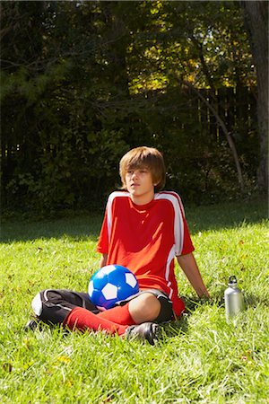 Teenage Boy Wearing Soccer Uniform Sitting on Grass Stock Photo - Rights-Managed, Code: 700-02757197