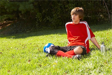 Teenage Boy Wearing Soccer Uniform and Sitting on Grass Stock Photo - Rights-Managed, Code: 700-02757198