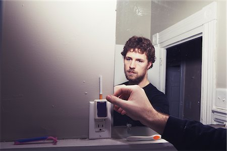 Man in Washroom Grabbing a Cigarette Stock Photo - Rights-Managed, Code: 700-02786862
