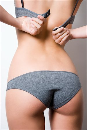 Woman in Underwear Putting on Her Bra Stock Photo - Rights-Managed, Code: 700-02798085