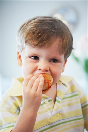 Close-up of Boy Eating Doughnut Stock Photo - Rights-Managed, Code: 700-02833652