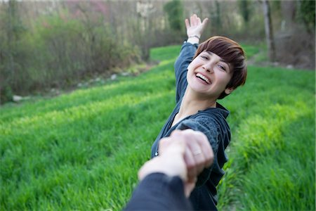 Happy Woman in a Field Holding Hands With Her Boyfriend Stock Photo - Rights-Managed, Code: 700-02887454