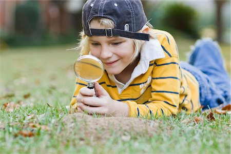 Little Boy Lying on Ground Holding Magnifying Glass Stock Photo - Rights-Managed, Code: 700-02912042