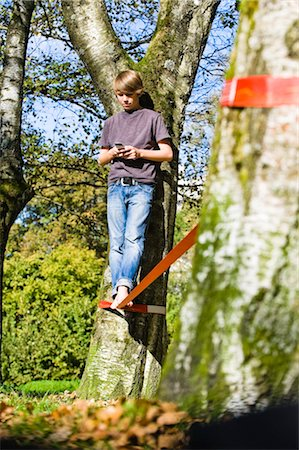 Boy Slacklining and Texting Stock Photo - Rights-Managed, Code: 700-03179177