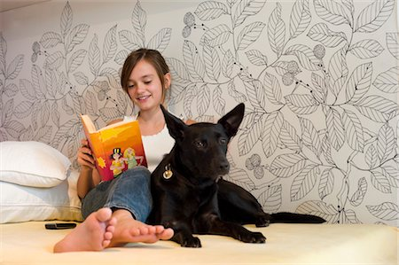 Teenage Girl Reading Book on Bed with Dog Stock Photo - Rights-Managed, Code: 700-03333121