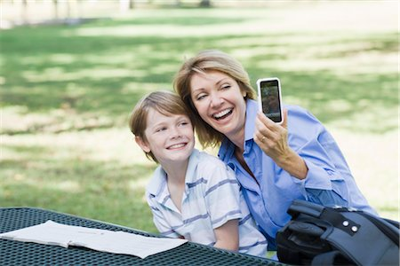 Mother and Son Sitting in Park using Cell Phone to Take a Picture of Themselves Stock Photo - Rights-Managed, Code: 700-03406475