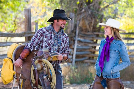 Cowboy Carrying Western Saddle and Talking with Cowgirl Stock Photo - Rights-Managed, Code: 700-03407357