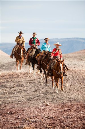 Group of Cowgirls and Cowboys Riding Horses through Badlands, Wyoming, USA Stock Photo - Rights-Managed, Code: 700-03407491