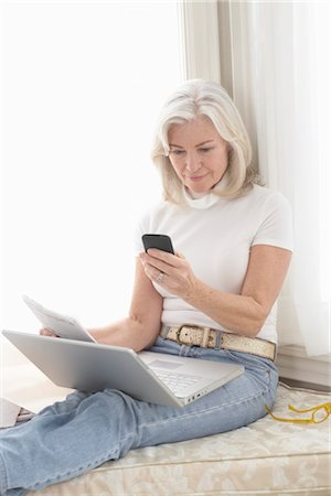 Woman at Home Using Laptop Computer and Sending Text Message Stock Photo - Rights-Managed, Code: 700-03439054