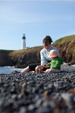 family fun day background - Mother and Baby Daughter Sitting on Beach, with Yaquina Head Lighthouse in the Distance, Near Newport, Oregon, USA Stock Photo - Rights-Managed, Code: 700-03439521