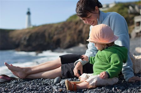 family fun day background - Mother and Baby Daughter Sitting on Beach, with Yaquina Head Lighthouse in the Distance, near Newport, Oregon, USA Stock Photo - Rights-Managed, Code: 700-03439522
