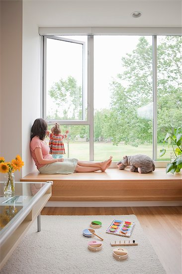 Mother and Young Daughter Sitting by Window inside Home Stock Photo - Premium Rights-Managed, Artist: Ty Milford, Image code: 700-03439556