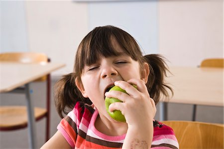 school desk - Girl in Class Eating an Apple Stock Photo - Rights-Managed, Code: 700-03445045