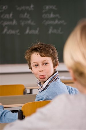 photo of class with misbehaving kids - Student Sticking His Tongue Out at His Classmate Stock Photo - Rights-Managed, Code: 700-03445055