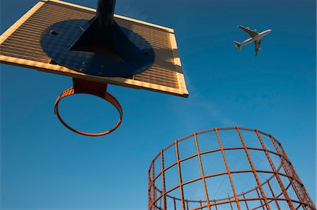 Basketball Hoop, an Empty Gasometer and Jet Plane Against Blue Sky Stock Photo - Rights-Managed, Code: 700-03446061