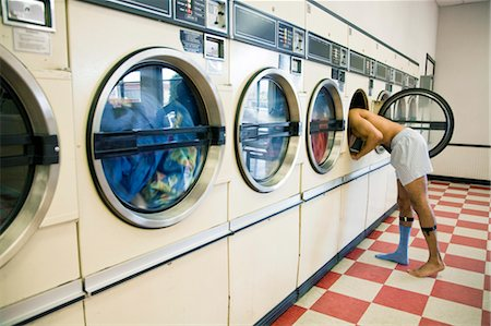 Man Leaning into Clothes Dryer in Laundromat Stock Photo - Rights-Managed, Code: 700-03456955