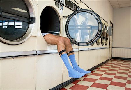 Man Lying in Clothes Dryer in Laundromat Stock Photo - Rights-Managed, Code: 700-03456964