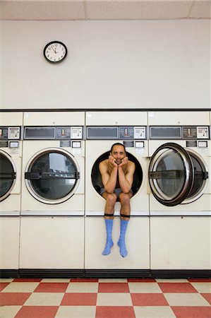 Man Sitting in Clothes Dryer in Laundromat Stock Photo - Rights-Managed, Code: 700-03456965