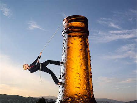 Businesswoman Climbing up Beer Bottle Stock Photo - Rights-Managed, Code: 700-03466491