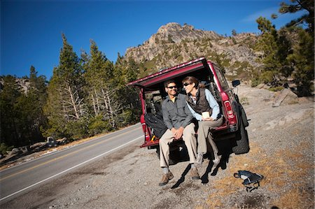 Couple Sitting on Tailgate of 4x4 Vehicle, Donner Summit, near Lake Tahoe, California, USA Stock Photo - Rights-Managed, Code: 700-03503010